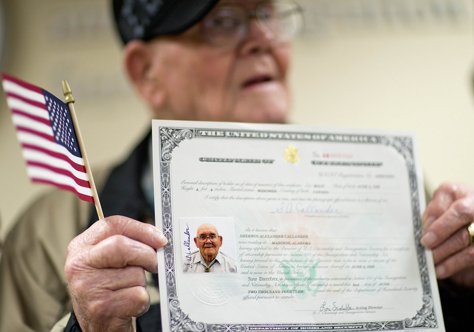 Photo - Ninety-four-year-old World War II veteran Sherwin Callander holds up his U.S. citizenship certificate following a naturalization ceremony, Monday, June 2, 2014, in Atlanta. The World War II veteran from Alabama is headed to France for D-Day ceremonies, a trip that seemed unlikely just last week. Callander read about ceremonies for the 70th anniversary of D-Day and thought it would be meaningful to go. He hadn't been back to France since landing on Utah Beach during the Battle of Normandy, but he hit a snag when he went to get a passport. Callander was born in Canada to an American mother, and his family moved to the U.S. when he was 3. But he didn't have documentation proving his U.S. citizenship. Federal officials heard his story and on Monday gave him a proof of citizenship certificate so he could get a passport in time to leave for France just hours later. (AP Photo/David Goldman)