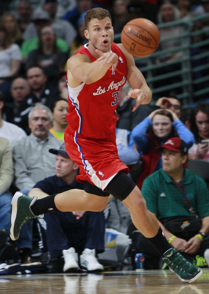 Photo - Los Angeles Clippers forward Blake Griffin reaches out to pull in a loose ball against the Denver Nuggets in the first quarter of an NBA basketball game in Denver on Monday, March 17, 2014. (AP Photo/David Zalubowski)