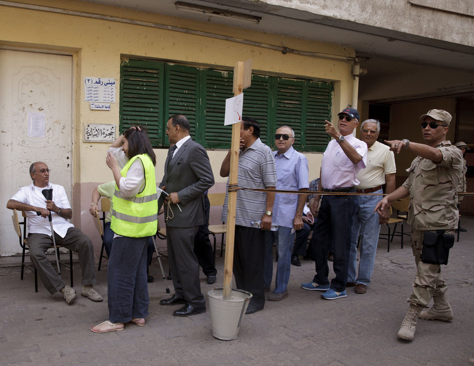Photo - An Egyptian soldier directs voters waiting to cast their ballots for President in an election that comes nearly a year after the military's ouster of the nation's first freely elected president, the Islamist Mohammed Morsi, in Cairo, Egypt, Monday, May 26, 2014. The man who removed Morsi, retired military chief Field Marshal Abdel-Fattah el-Sissi, is practically assured of a victory in the vote. (AP Photo/Maya Alleruzzo)