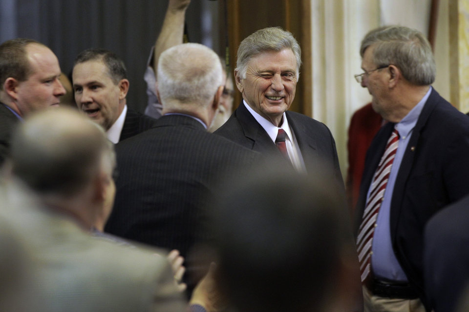 Arkansas Gov. Mike Beebe winks as he is greeted by legislators in the House chamber at the Arkansas state Capitol in Little Rock, Ark., before delivering his State of the State address Tuesday, Jan. 15, 2013. (AP Photo/Danny Johnston)