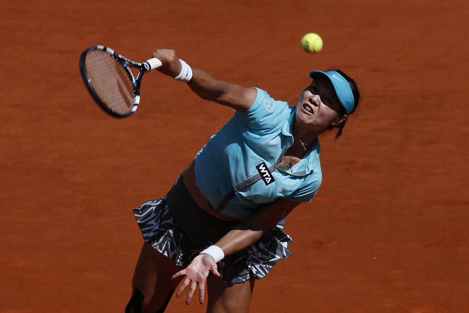 Photo - Na Li from China serves the ball during a Madrid Open tennis tournament match against Sloane Stephens from the U.S. in Madrid, Spain, Thursday, May 8, 2014 . (AP Photo/Daniel Ochoa de Olza)