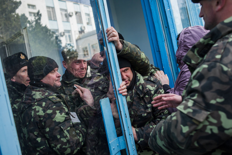 Photo - Pro-Russian self-defense force members get through an entrance to the Ukrainian Navy headquarters in Sevastopol, Crimea, Wednesday, March 19, 2014. An Associated Press photographer said several hundred militiamen took down the gate and made their way onto the base. They then raised the Russian flag in the square by the headquarters. The unarmed militia waited for an hour on the square before the move to storm the headquarters. Following the arrival of the commander of the Russian Black Sea fleet, the Crimeans took over the building. (AP Photo/Andrew Lubimov)