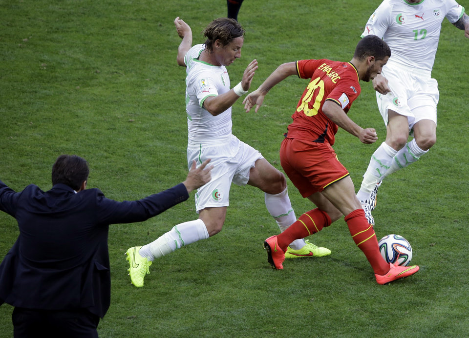 Photo - Belgium's Eden Hazard controls the ball past Algeria's Mehdi Mostefa as Belgium's head coach Marc Wilmots gestures on the sidelines during the group H World Cup soccer match between Belgium and Algeria at the Mineirao Stadium in Belo Horizonte, Brazil, Tuesday, June 17, 2014. (AP Photo/Sergei Grits)