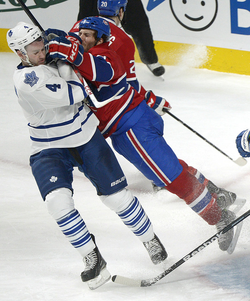 Montreal Canadiens' Brandon Prust, right, lunges at Toronto Maple Leafs' Cody Franson during the second period of an NHL hockey game in Montreal, Saturday, Feb. 9, 2013. (AP Photo/The Canadian Press, Graham Hughes)