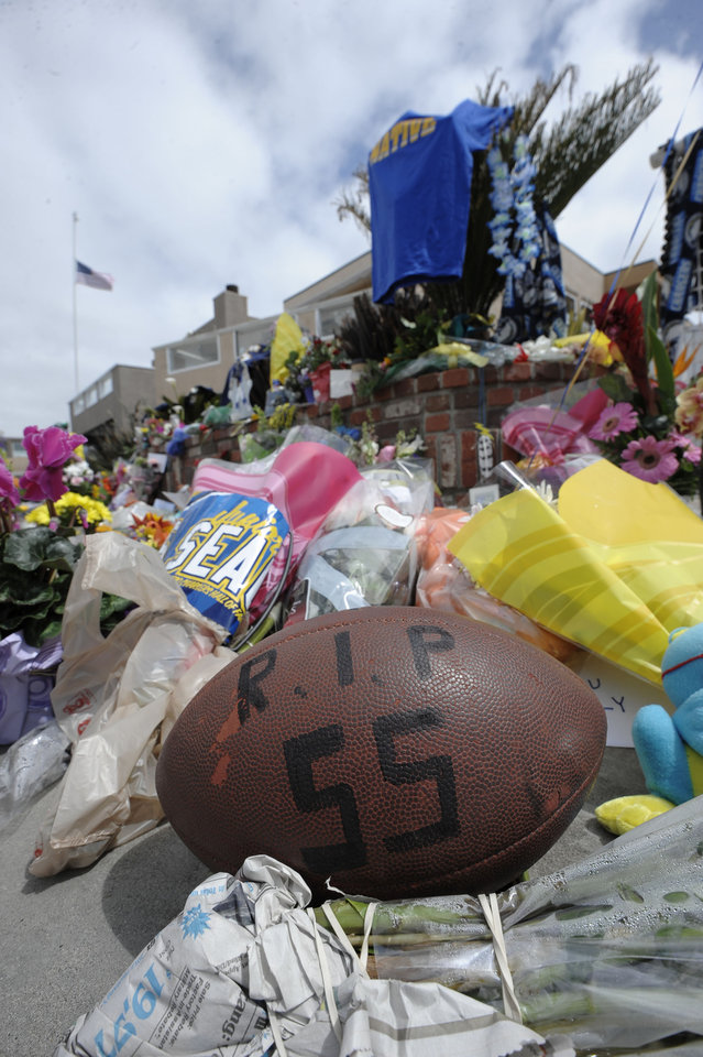 Photo -   A football with Junior Seau's number sits in front of a memorial in the driveway of the house of former NFL star Junior Seau Thursday, May 3, 2012, in Oceanside, Calif. Seau's death in Oceanside, in northern San Diego County, stunned the region he represented with almost reckless abandon. (AP Photo/Denis Poroy)