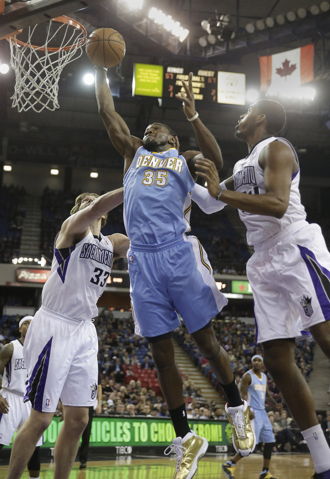 Denver Nuggets forward Kenneth Faried, center, grabs a rebound between Sacramento Kings\' Aaron Gray, left, and Jason Thompson during the first quarter of an NBA basketball game in Sacramento, Calif., Sunday, Jan. 26, 2014. (AP Photo/Rich Pedroncelli)