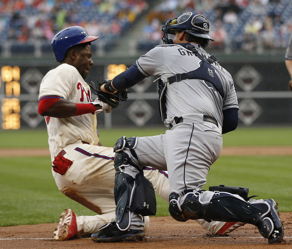 Photo - Philadelphia Phillies' John Mayberry Jr., left, is tagged out at home plate by San Diego Padres catcher Yasmani Grandal after trying to score on a fielders choice by Wil Nieves during the fourth inning of a baseball game, Thursday, June 12, 2014, in Philadelphia. Nieves was safe at first base on the play. (AP Photo/Matt Slocum)