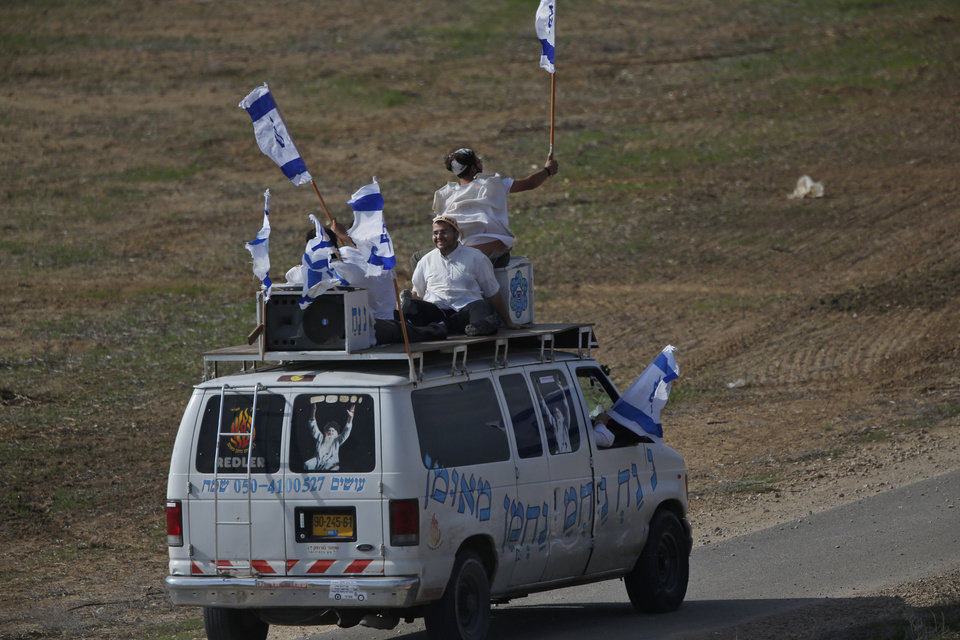 Photo -   Ultra-Orthodox Jews of the Bratslav Hasidic sect, in support of the Israeli forces, hold national flags on top of a van with the name of their spiritual leader Rabbi Nachman of Uman, right, as they drive towards the border with the central Gaza Strip, Monday, Nov. 19, 2012. Israeli aircraft struck crowded areas in the Gaza Strip and killed a senior militant with a missile strike on a media center Monday, driving up the Palestinian death toll to 96, as Israel broadened its targets in the 6-day-old offensive meant to quell Hamas rocket fire on Israel. (AP Photo/Lefteris Pitarakis)