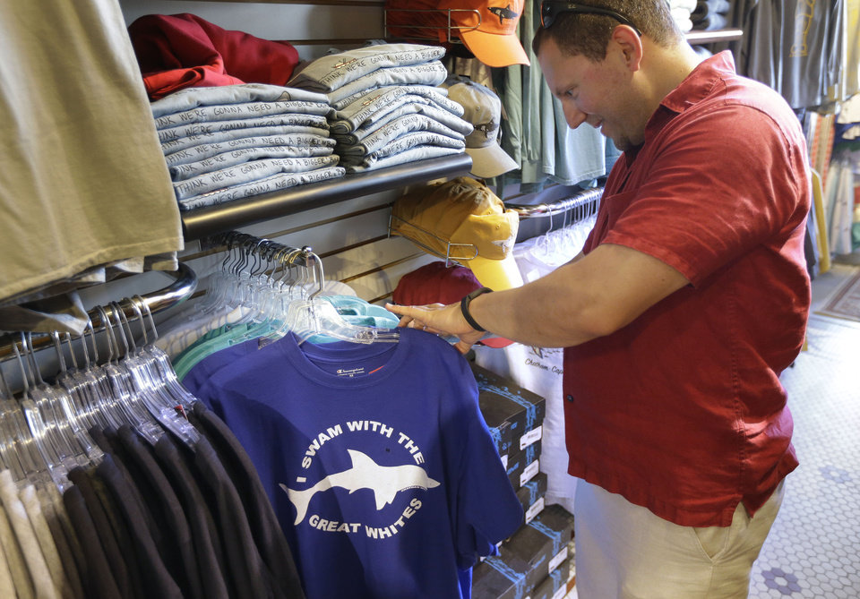 Photo - In this July 2, 2014 photo, vacationer Mark McCurdy, of Everett, Mass., examines shark-themed clothing at the Chatham Clothing Bar in Chatham, Mass. Growing sightings of great white sharks off Cape Cod are generating business for local entrepreneurs as residents and tourists seek a glimpse of the offshore predators -- or purchase their shark-themed memorabilia and apparel. (AP Photo/Steven Senne)