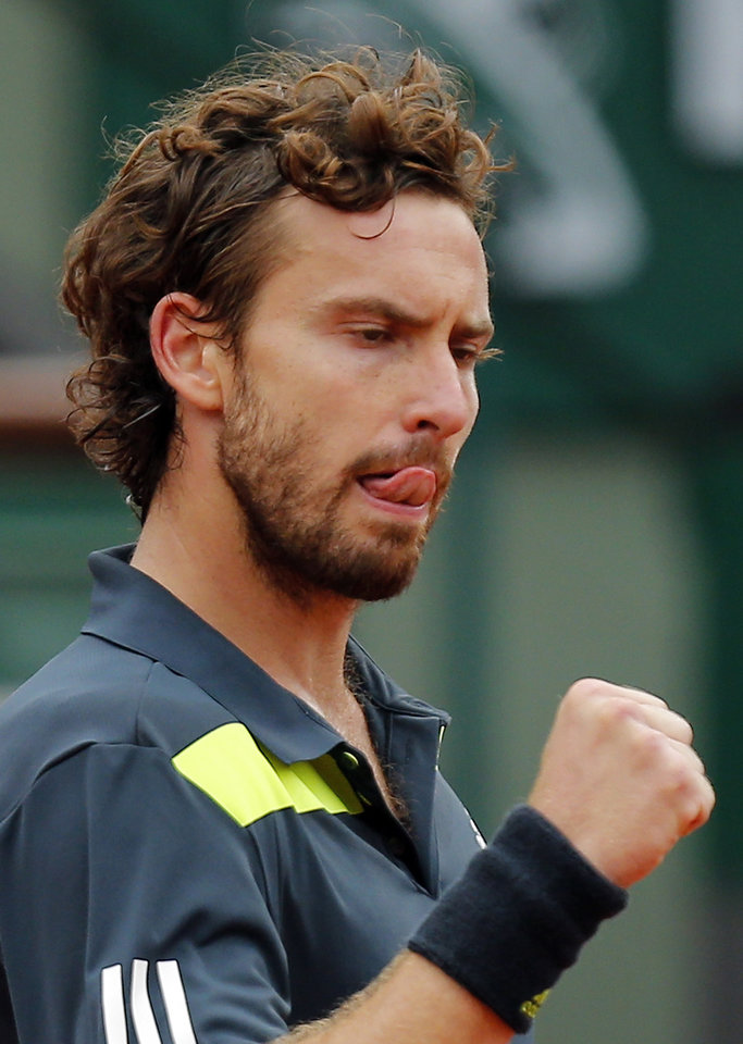 Photo - Latvia's Ernests Gulbis clenches his fist as he plays Switzerland's Roger Federer during their fourth round match of  the French Open tennis tournament at the Roland Garros stadium, in Paris, France, Sunday, June 1, 2014. (AP Photo/David Vincent)