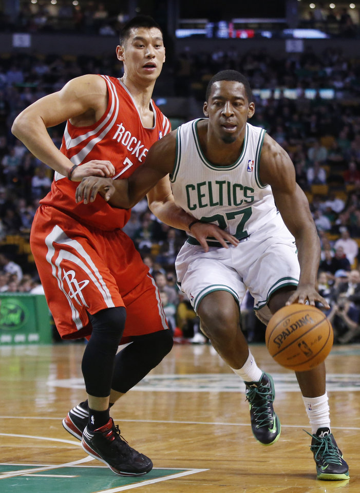 Photo - Boston Celtics shooting guard Jordan Crawford, right, gets by Houston Rockets point guard Jeremy Lin (7) in the first half of an NBA basketball game in Boston, Monday, Jan. 13, 2014. (AP Photo/Elise Amendola)