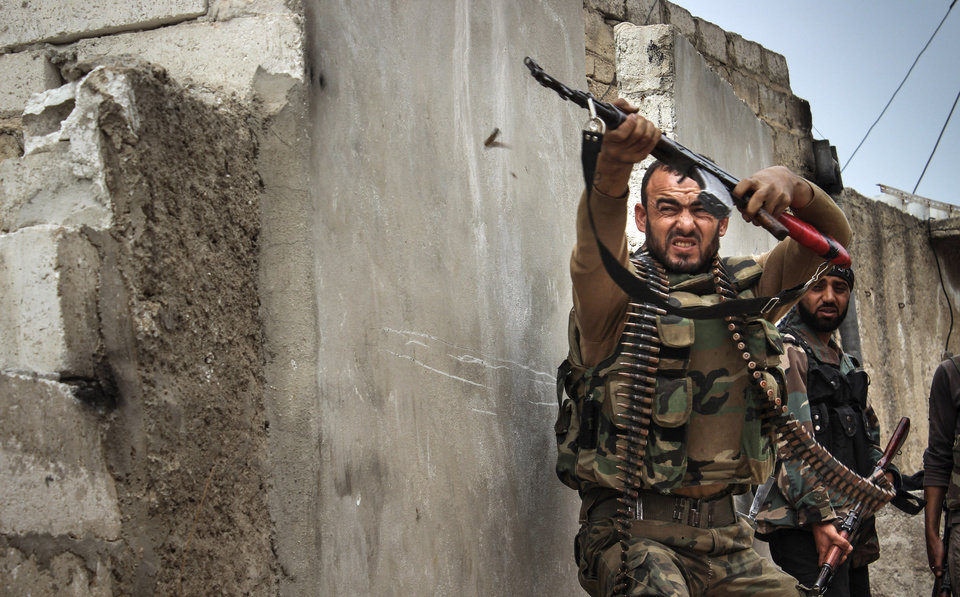 Photo -   In this Tuesday, Oct. 30, 2012 photo, a Syrian rebel fires at sniper positions in the town of Harem, Syria, near the Turkish border. (AP Photo/Mustafa Karali)