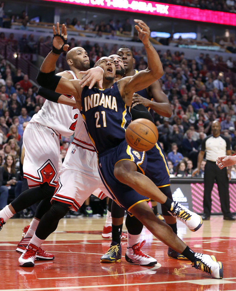 Photo - Indiana Pacers forward David West (21) is fouled by Chicago Bulls forward Carlos Boozer during the second half of an NBA basketball game Monday, March 24, 2014, in Chicago. The Bulls won 89-77. (AP Photo/Charles Rex Arbogast)