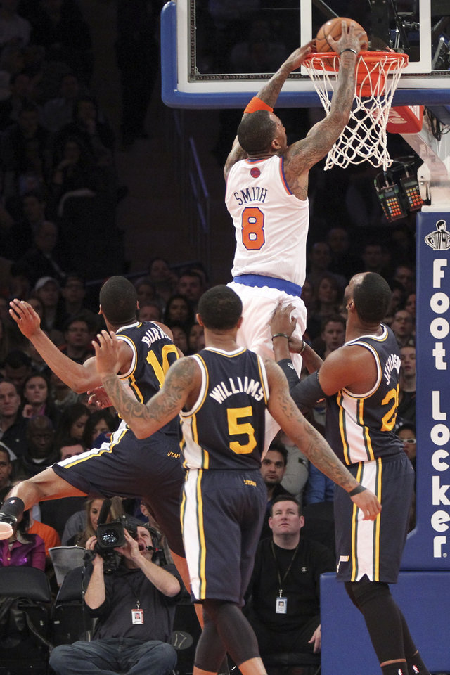 New York Knicks' J.R. Smith (8) dunks as Utah Jazz's Al Jefferson (25), Mo Williams (5) and Alec Burks watch during the first half of an NBA basketball game on Saturday, March 9, 2013, at Madison Square Garden in New York. (AP Photo/Mary Altaffer)