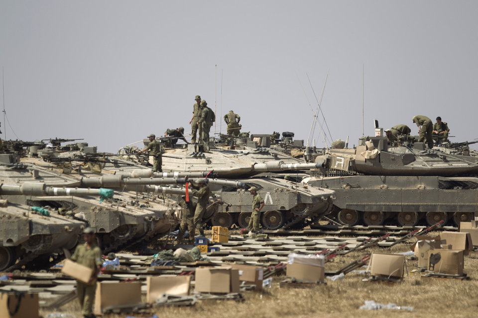 Photo - Israeli soldiers work on their tanks near the Israel and Gaza Strip border, Monday, July 7, 2014. The Islamic militant group Hamas that rules Gaza vowed revenge on Israel for the death of several of its members killed in an airstrike early Monday morning in the deadliest exchange of fire since the latest round of attacks began weeks ago.(AP Photo/Ariel Schalit)
