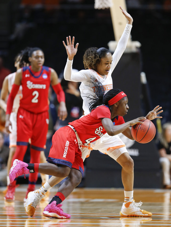 Photo - St. John's guard Aaliyah Lewis (4) drives against Tennessee guard Meighan Simmons, top, in the first half of an NCAA women's college basketball second-round tournament game Monday, March 24, 2014, in Knoxville, Tenn. (AP Photo/John Bazemore)