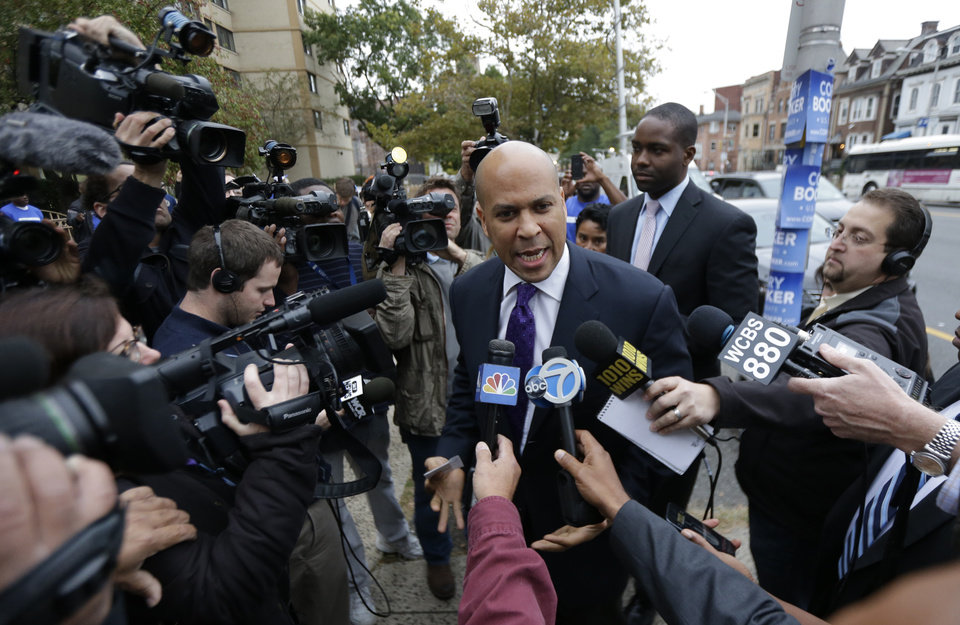 Photo - Newark Mayor Cory Booker, center, talks to media outside of a polling place before casting his vote in a special election for the vacant New Jersey seat in the U.S. Senate, Wednesday, Oct. 16, 2013, in Newark, N.J. Booker is going up against Republican Steve Lonegan. (AP Photo/Julio Cortez)