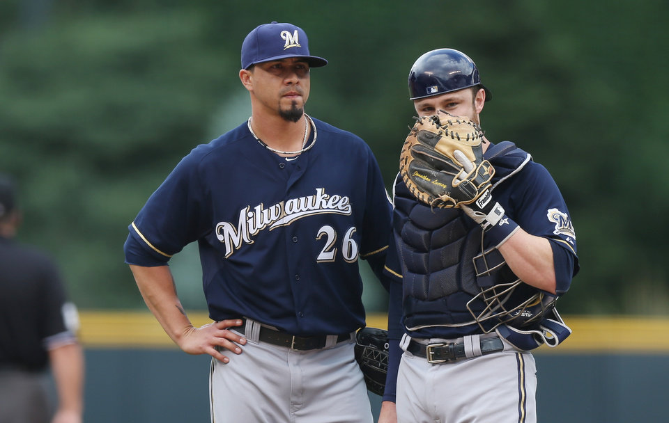 Photo - Milwaukee Brewers starting pitcher Kyle Lohse, left, confers with catcher Jonathan Lucroy after Colorado Rockies' Charlie Blackmon stole second base in the first inning of a baseball game in Denver on Sunday, June 22, 2014. (AP Photo/David Zalubowski)