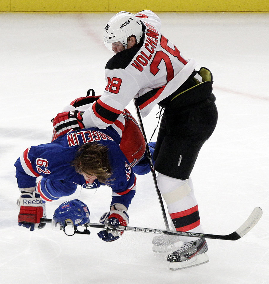 Photo -   New Jersey Devils' Anton Volchenkov (28) and New York Rangers' Carl Hagelin (62) collide during the second period of Game 2 of the NHL hockey Stanley Cup Eastern Conference final playoff series, Wednesday, May 16, 2012, in New York. (AP Photo/Frank Franklin II)