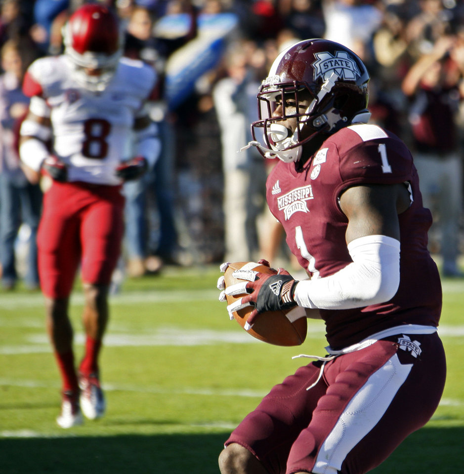 Photo -   Mississippi State wide receiver Chad Bumphis (1) leaps into the end zone ahead of Arkansas cornerback Tevin Mitchel (8) with a 22-yard touchdown pass reception in the fourth quarter of their NCAA college football game in Starkville, Miss., Saturday, Nov. 17, 2012. Mississippi State won 45-14. (AP Photo/Rogelio V. Solis)