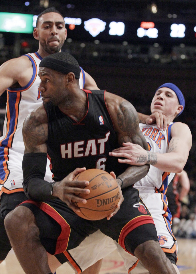 Photo -   Miami Heat's LeBron James spins away from New York Knicks' Mike Bibby, right, and Jared Jeffries, left, during the first half of Game 4 of an NBA basketball first-round playoff series at Madison Square Garden, Sunday, May 6, 2012, in New York. (AP Photo/Frank Franklin II)