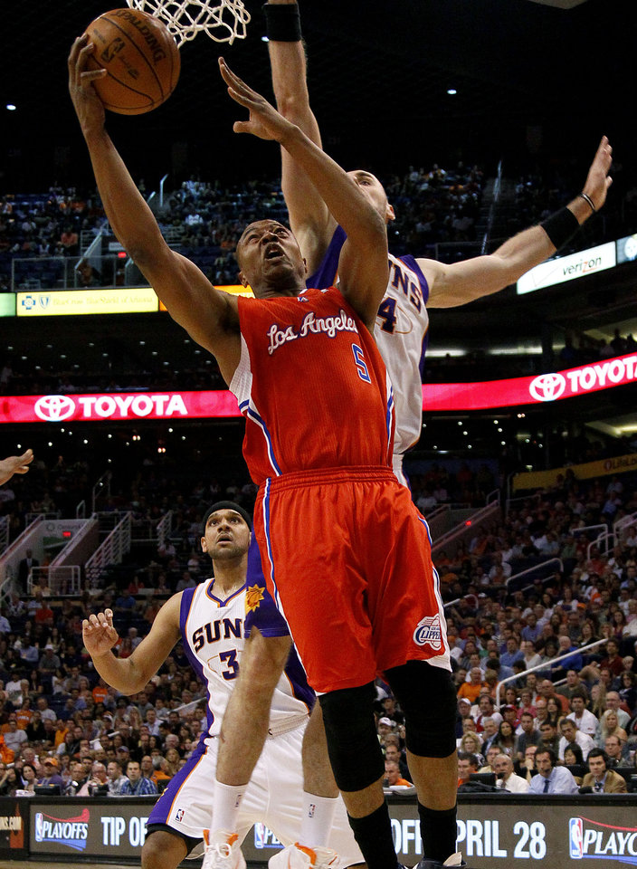 Photo -   Los Angeles Clippers' Caron Butler shoots past Phoenix Suns' Marcin Gortat (4), of Poland, during the first half of an NBA basketball game, Thursday, April 19, 2012, in Phoenix. (AP Photo/Matt York)