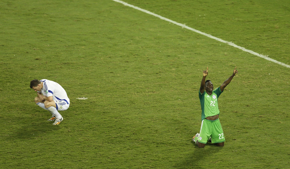 Photo - Nigeria's Kenneth Omeruo, right, celebrates as Bosnia's Edin Dzeko, left, sits on the pitch after the group F World Cup soccer match between Nigeria and Bosnia at the Arena Pantanal in Cuiaba, Brazil, Saturday, June 21, 2014. Nigeria eliminated Bosnia-Herzegovina from World Cup contention with a 1-0 win over the tournament newcomers. (AP Photo/Fernando Llano)