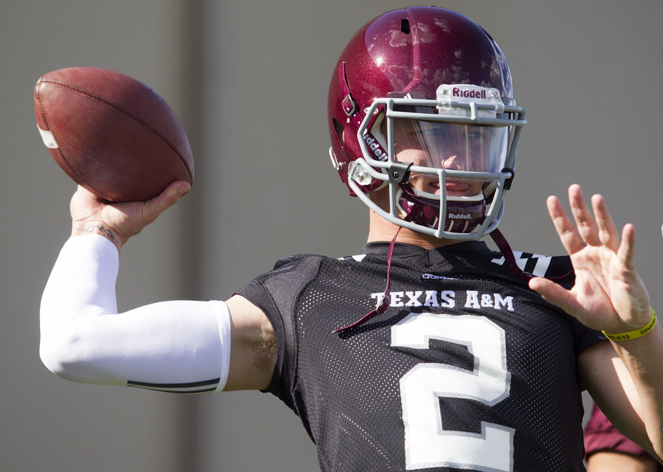 Photo - Texas A&M quarterback and Heisman Trophy winner Johnny Manziel throws during football practice, Monday, Aug. 5, 2013, in College Station, Texas. The NCAA has started an investigation as to whether Manziel received payment for signing hundreds of autographs on photos and sports memorabilia in January. (AP Photo/Patric Schneider)