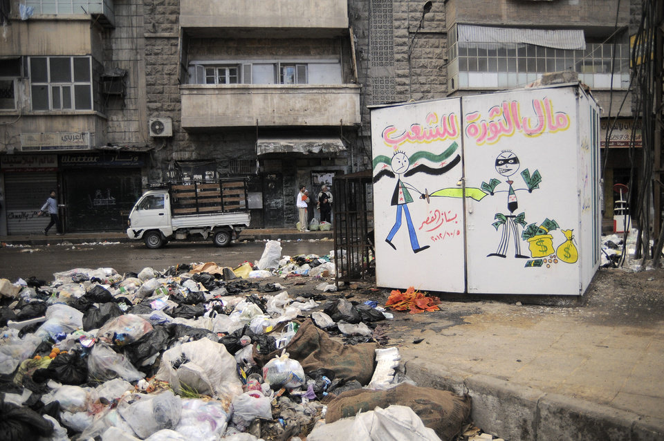 In this Saturday, Nov. 10, 2012 photo, garbage is plied up in the Al-Buhouth area of Aleppo, Syria. The Arabic writing on the kiosk at right reads,