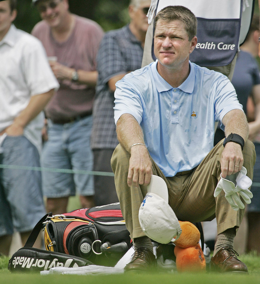 Photo - Scott Verplank sits on his bag and waits on the seventh tee for Ben Crane to hit at Brown Deer Park during the third round of the U.S. Bank Championship Saturday, July 23, 2005, in Milwaukee.  (AP Photo/Morry Gash)