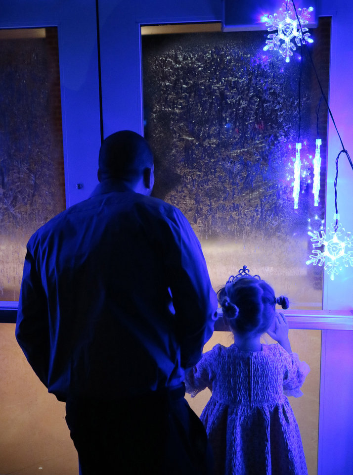 Photo -  Jason Akin looks out a frosted door with his daughter, Brody, 5, during the Daddy-Daughter Dance with a Frozen theme hosted by Edmond Park and Recreation Department in February. [PHOTO BY DOUG HOKE, THE OKLAHOMAN]