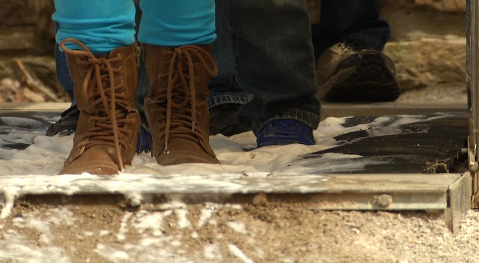 Photo - In this image from video, visitors to Mammoth Cave National Park in Mammoth Cave, Ky., walk over bio-security mats at the conclusion of cave tours to help contain the spread of white-nose syndrome. The disease that has killed more than 6 million cave-dwelling bats in the United States is on the move and wildlife biologists are worried. It gets its name from a white fungus that's found on the muzzles, ears and wings of infected bats. In Tennessee, some caves are closed to the public. At Mammoth Cave National Park, visitors are required to scrub their shoes after cave tours. Wildlife biologists say the threat is real -- there is no known way to stop the spread. (AP Photo/Alex Sanz)