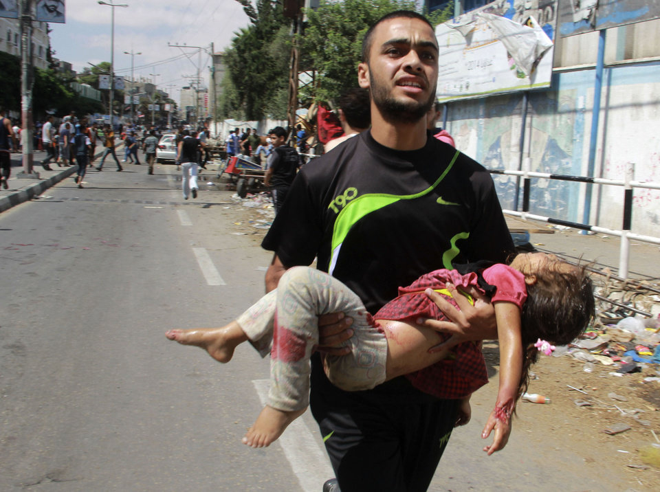 Photo - A Palestinian man carries a child killed in a blast outside a UN run school in Rafah, in the southern Gaza Strip, Sunday, Aug. 3, 2014. UNRWA's Director of Operations in the Gaza Strip said preliminary findings indicated the blast was a result of an Israeli airstrike near the school that been providing shelter for some 3,000 people. (AP Photo/Hatem Ali)