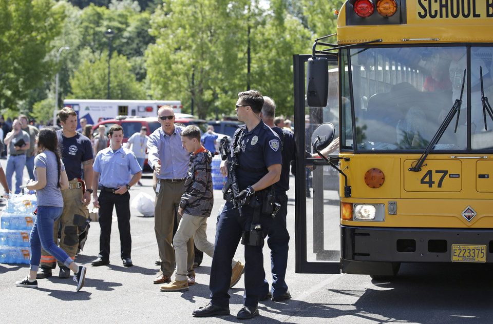 Photo - A police officer stands guard as students arrived at a shopping center parking lot in Wood Village, Ore., after a shooting at Reynolds High School Tuesday, June 10, 2014, in nearby Troutdale. A gunman killed a student at the high school east of Portland Tuesday and the shooter is also dead, police said. (AP Photo/Rick Bowmer)