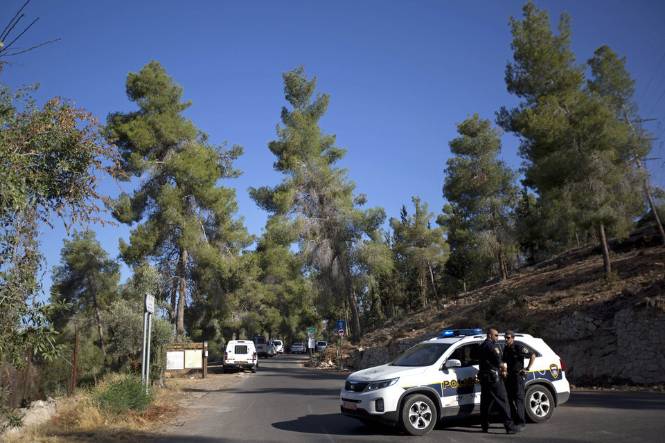 Photo - Israeli police officers block the entrance to a forest, where a body was found, in Jerusalem, Wednesday, July 2, 2014. Israeli police say Palestinians and Israeli forces have clashed following reports that an Arab teen was kidnapped and a body was found in a Jerusalem forest.  Police spokesman Micky Rosenfeld said police received reports Wednesday that an Arab teen was forced into a car. A body was later found, but police have not yet established whether the two incidents are related. (AP Photo/Sebastian Scheiner)