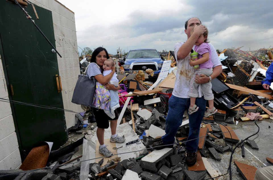 Photo - Homes in the McCulley Mill Rd. area near Athens, Ala., are completely destroyed following a large tornado that cut a path through Lawrence, Morgan and Limestone Counties Wednesday, April 27, 2011.  Kevin Harrison and his wife Sara Beth hold their children, Mason and Sophie as they emerge from a safe room, the only thing that survived of their house.  (AP Photo/The Decatur Daily, Gary Cosby Jr.)