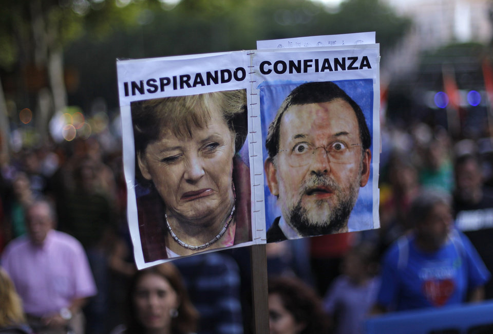 "Protestors hold a banner with a photo of German Prime Minister Angela Merkel and Spanish Prime Minister Mariano Rajoy reading ""inspiring confidence"" as they march against healthcare austerity measures announced by the Spanish government in Madrid, Spain, Saturday, Oct. 6, 2012. Hundreds of Spaniards concerned with government cuts to healthcare and civil servants hit with another freeze on their wages for next year hold a protest in downtown Madrid. (AP Photo/Andres Kudacki)"