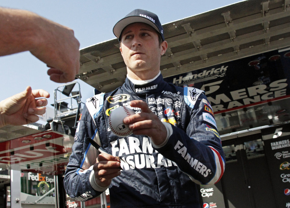Driver Kasey Kahne autographs a baseball for a fan during practice for the NASCAR Sprint Cup series auto race in Fontana, Calif., Saturday, March 23, 2013.  (AP Photo/Reed Saxon)