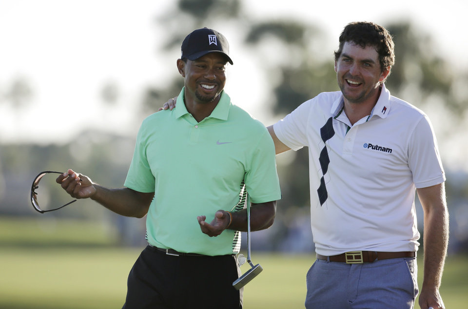 Photo - Tiger Woods, left, and Keegan Bradley, right, laugh on the 18th green after completing the second round of the Honda Classic golf tournament, Friday, Feb. 28, 2014, in Palm Beach Gardens, Fla. (AP Photo/Lynne Sladky)