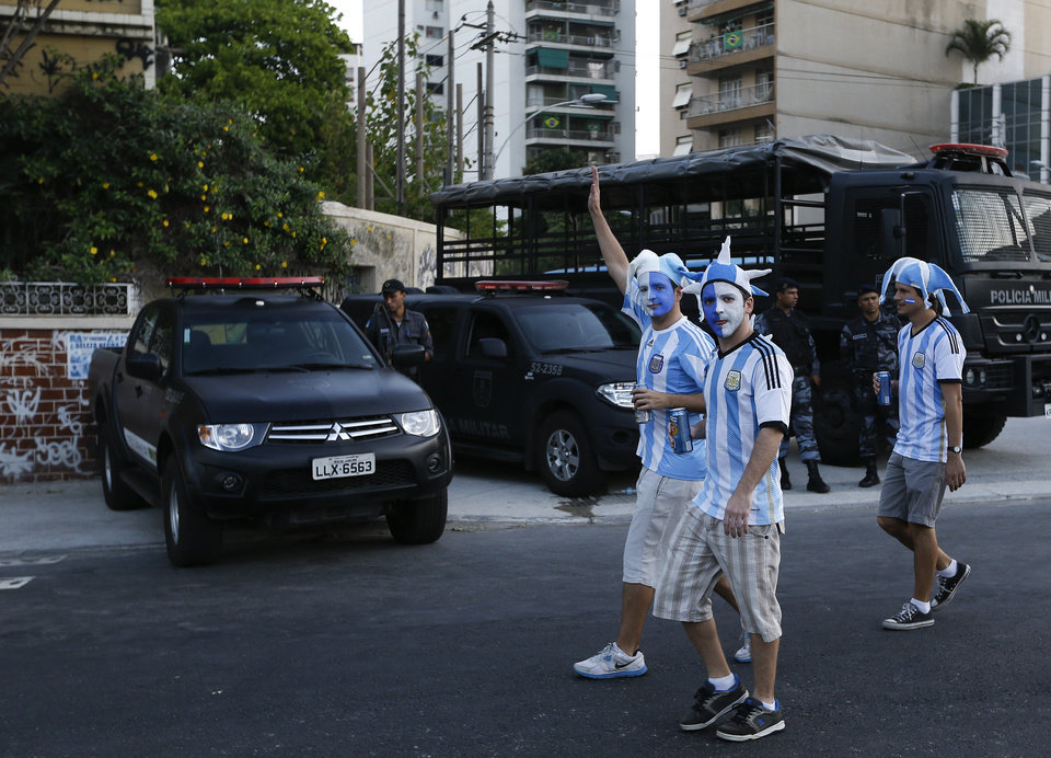 Photo - Argentina fans walk past police outside the stadium ahead of the group F World Cup soccer match between Argentina and Bosnia at the Maracana Stadium in Rio de Janeiro, Brazil, Sunday, June 15, 2014.  (AP Photo/Kirsty Wigglesworth)
