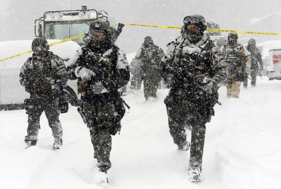 Photo - A San Bernardino County Sheriff SWAT team returns to the command post at Bear Mountain near Big Bear Lake, Calif. after searching for Christopher Jordan Dorner on Friday, Feb. 8, 2013. Search conditions have been hampered by a heavy winter storm in the area. Dorner, a former Los Angeles police officer, is accused of carrying out a killing spree because he felt he was unfairly fired from his job. (AP Photo/Pool, The Inland Valley Daily Bulletin, Will Lester)