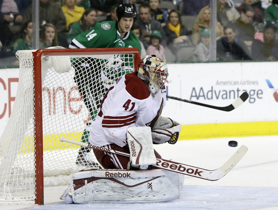 Photo - Phoenix Coyotes goalie Mike Smith (41) keeps his eyes on a shot from the Dallas Stars as Jamie Benn (14) watches from behind the net in the first period of an NHL hockey game, Saturday, Feb. 8, 2014, in Dallas. (AP Photo/Tony Gutierrez)