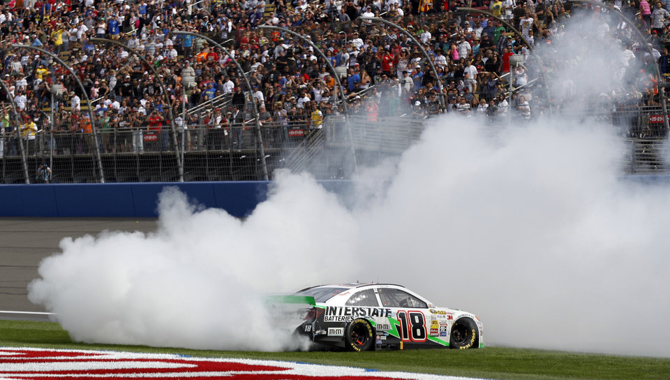 Photo - Kyle Busch (18) does a burnout after winning the NASCAR Sprint Series auto race in Fontana, Calif., Sunday, March 23, 2014.  (AP Photo/Alex Gallardo)