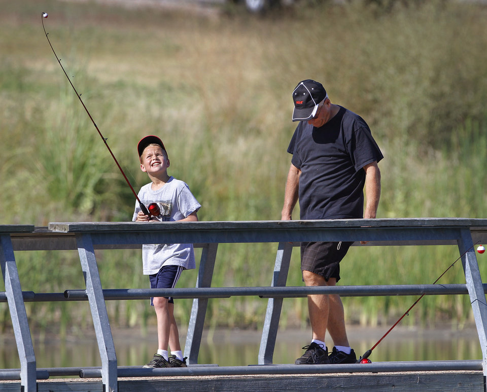 A young boy looks up at the end of his  pole as he and a man walk along the fishing pier after they finished fishing. The Oklahoma City Police Athletic League and the Oklahoma City  parks department teamed up to organize a fishing clinic for kids, aged  5-15, Saturday morning, July 12, 2012.  Organizers at the event said 50 children showed up to cast their fishing lines and lures into Crystal Lake on SW 15, west of MacArthur Blvd.  Most children were accompanied by an adult.   Photo by Jim Beckel, The Oklahoman.