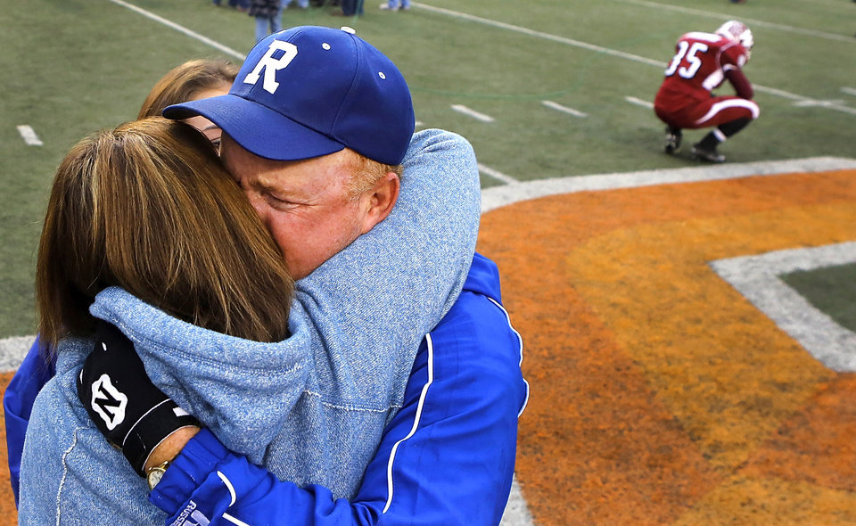 A dejected Wynnewood player copes with his team\'s loss as Ringling Assistant Coach Richie Gandy celebrates his team\'s win with hugs and tears. Ringling Blue Devils defeated Wynnewood, Savages 39-12 in the Class A High School football championship game at Boone Pickens Stadium in Stillwater on Saturday, Dec. 8, 2012. Photo by Jim Beckel, The Oklahoman