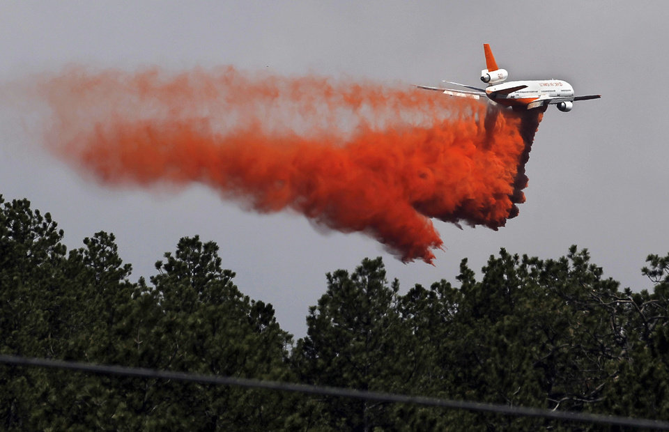 Photo - A fire-fighting slurry plane makes a pass in preparation drops its load on a wildfire in the Black Forest area north of Colorado Springs, Colo., on Wednesday, June 12, 2013. The number of houses destroyed by the Black Forest fire could grow to around 100, and authorities fear it's possible that some people who stayed behind might have died. (AP Photo/Brennan Linsley)