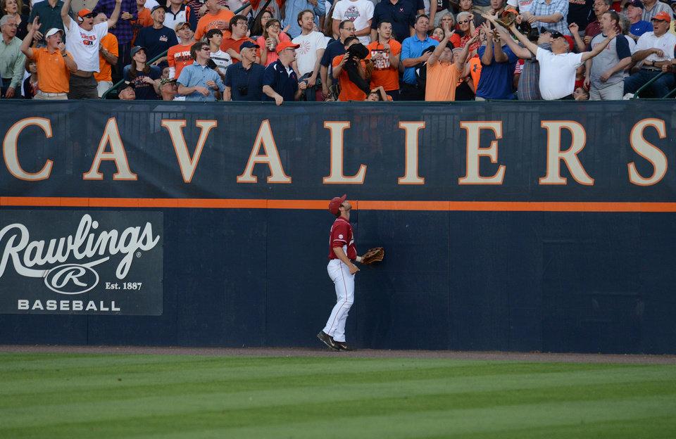Photo - Arkansas' Tyler Spoon watches as a ball hit by Virginia's Mike Papi sails out of the park during the first inning of an NCAA college baseball regional tournament game in Charlottesville, Va., Saturday, May 31, 2014. (AP Photo/Pat Jarrett)