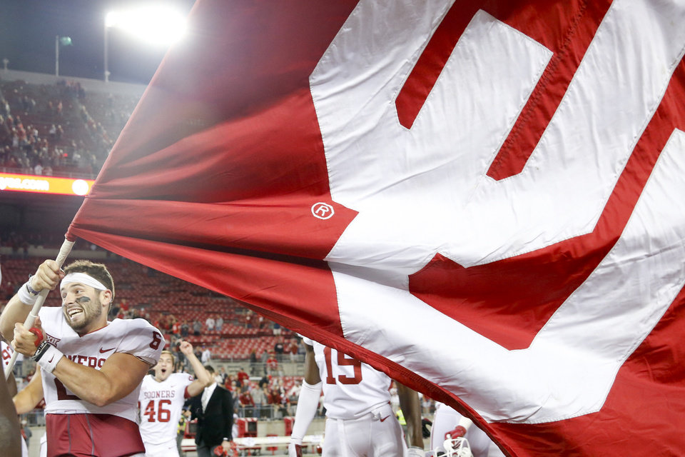 Photo - Oklahoma Sooners quarterback Baker Mayfield (6) waves an Oklahoma University flag at midfield after his team's win over Ohio State at Ohio Stadium in Columbus, Ohio on Saturday, September 9, 2017. IAN MAULE/Tulsa World