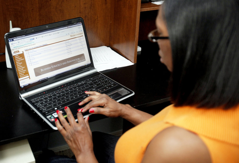 Photo - Quita Tucker works on an assignment Wednesday for online classwork at Walden University in Edmond. PHOTO BY SARAH PHIPPS, THE OKLAHOMAN