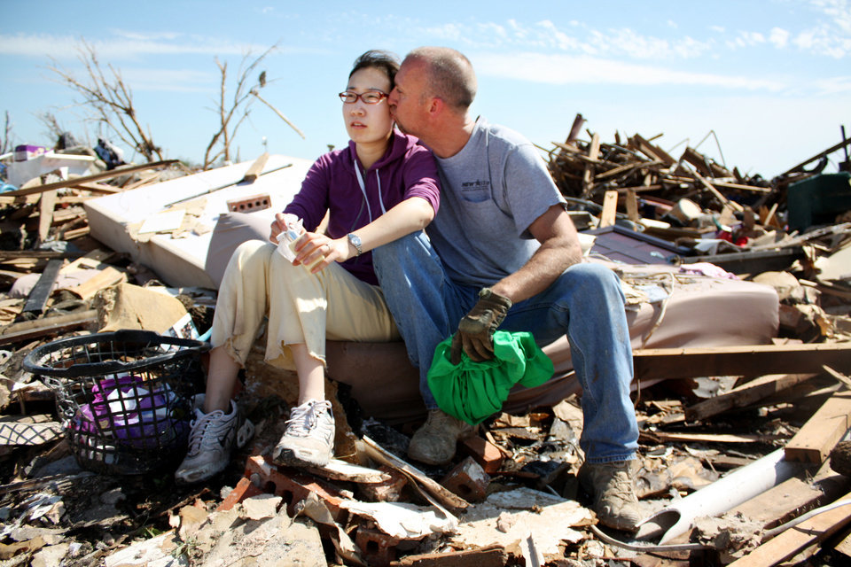 Curt Garrison and his fiance Wie Lu sit on their bed amid the rubble of their old home in Moore. Lu is visiting Garrison from China. She is in the process of getting her fiance visa so the couple can marry, but the paperwork was lost when the home was destroyed in the May 20 tornado. Photo by Adam Kemp, The Oklahoman